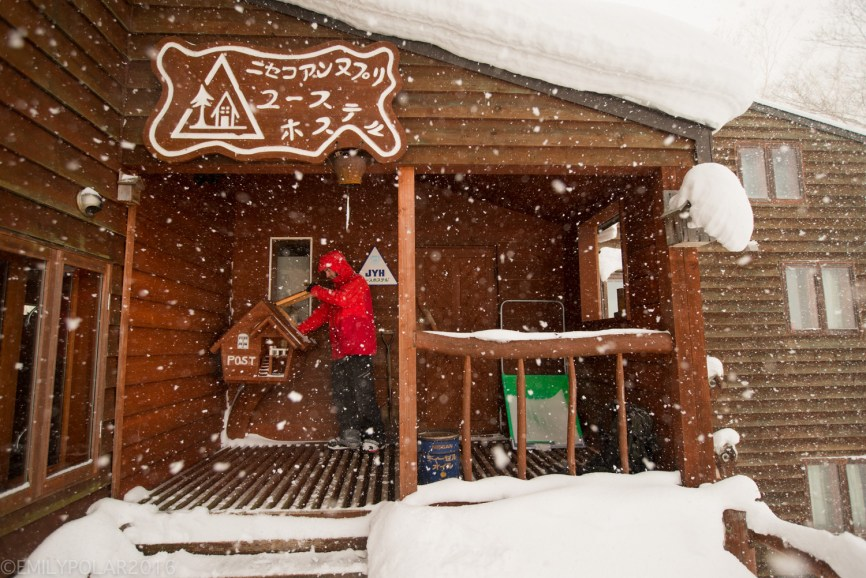 Man checking mail at hostel in the dumping snow of Niseko, Japan.