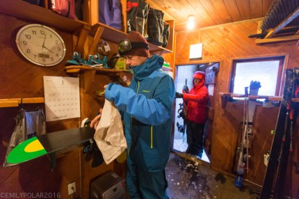 Snowboarder waxing and brushing his board in the dry room at the base of Annupuri in Niseko, Japan.