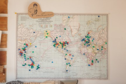 World map hanging up at The Day cafe with color pins marking where people are from in the world.
