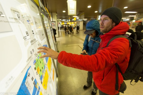 Boys on snowboard trip in Japan look at map and phones in train station to find their way to Niseko.