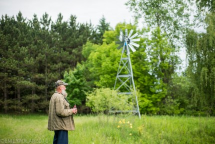 Man standing with a beer in a green forest on his land with a windmill in Wisconsin.