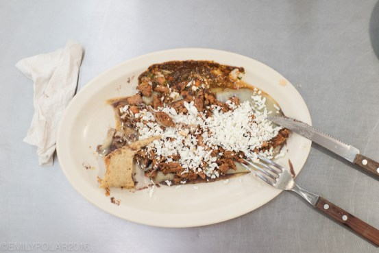 Plate of tacos with beans and cheese in Mercado de Medellin in Mexico City.