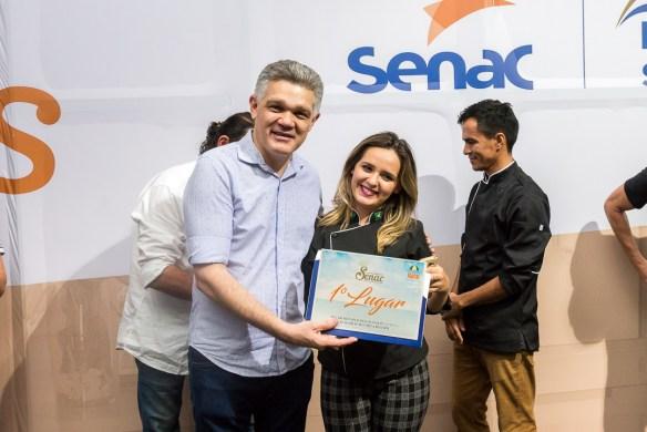Fernando Virgílio, diretor do Senac, entrega prêmio à vencedora do festival
