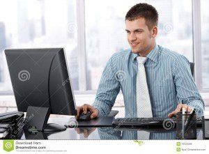 hombre-de-negocios-joven-que-trabaja-en-la-sonrisa-moderna-de-la-oficina-19423399