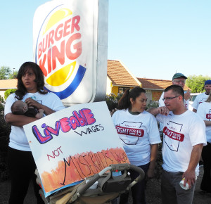 Fast food worker at a Fight for $15 rally with her baby.