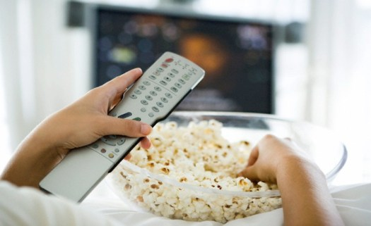 Person watching television, holding remote control and bowl of popcorn, cropped view --- Image by © Ale Ventura/PhotoAlto/Corbis