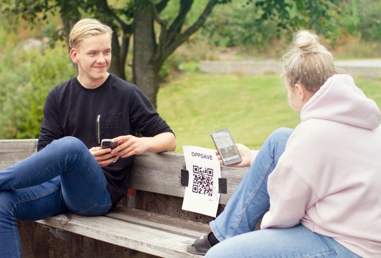 Gutt og jente sitter på parkbenk med mobiler. En lapp er hengt opp på benken med en QR kode som jenta scanner med mobilen.