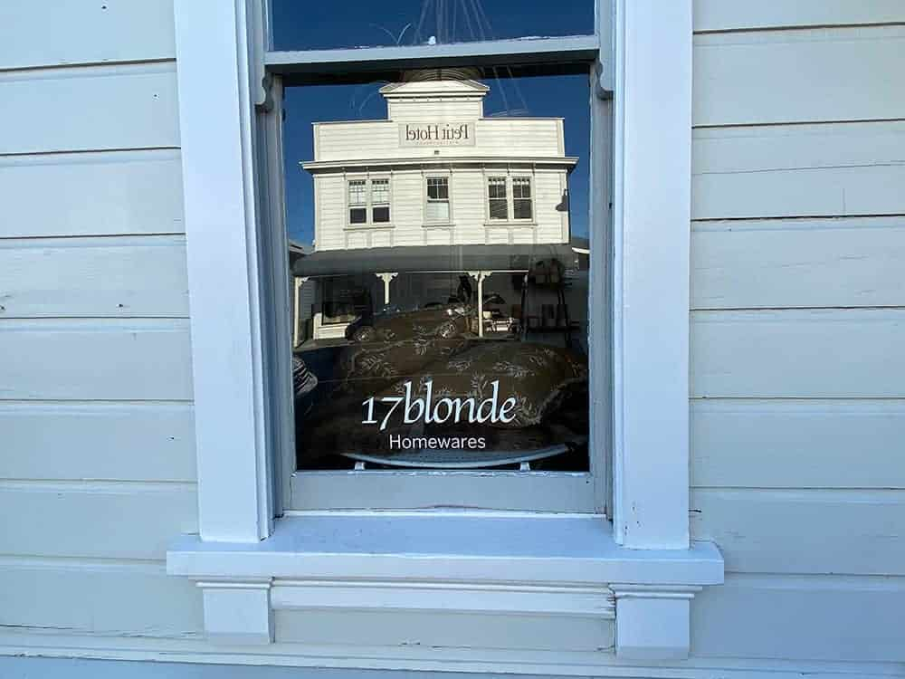 The Petit Hotel reflected in 17 Blonde Homewares window