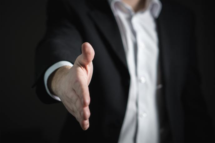 Salesman in a suit, extending handshake towards camera.