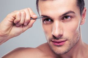 A man tweezing his eyebrows
