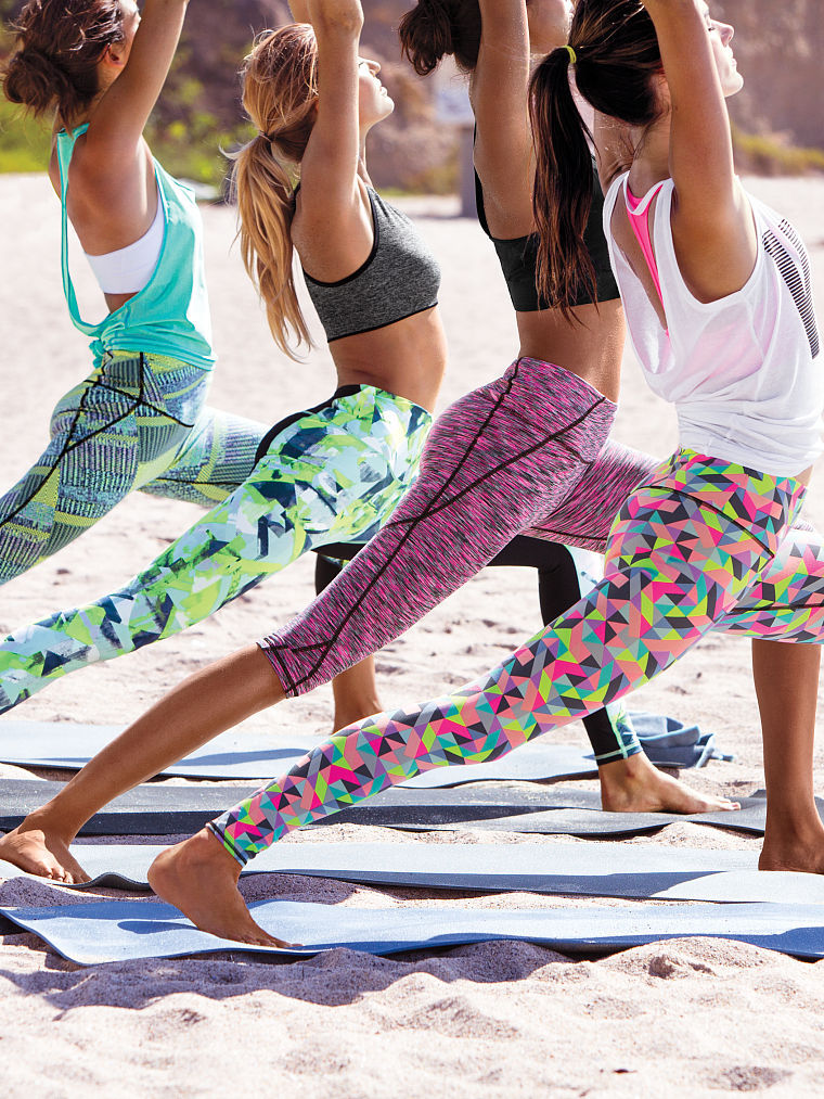 fitness tips: women doing yoga on the beach in colourful leggings
