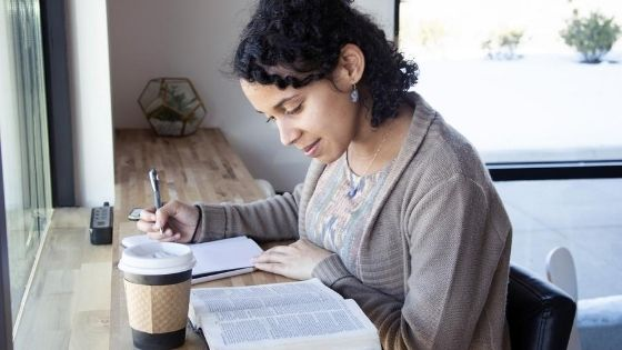 woman-reading-the-bible-with-a-cup-of-coffee-on-the-table-next-to-the-bible-1