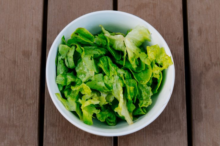 Bowl of green lettuce leaves on wooden tabletop