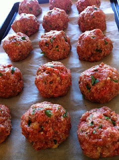 sheet pan with parchment paper and raw meatballs ready to flash freeze for the freezer