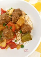 sweet and sour meatballs over rice in white bowl
