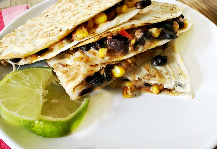 Black Bean and Roasted Corn Quesadillas served on a white plate with a lime slice