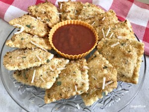 Air Fryer Fried Ravioli on a crystal plate with marinara dipping sauce, with a red checkered towel