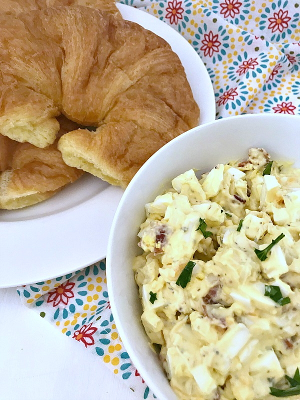 Bacon Cheddar Egg Salad in white bowl with a plate of crossiants beside it
