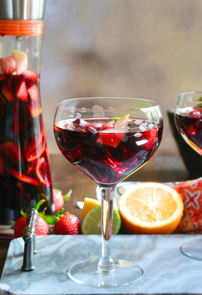 Spanish Sangria in a wine glass with fruit in it. Carafe of Spanish Sangria beside the glass