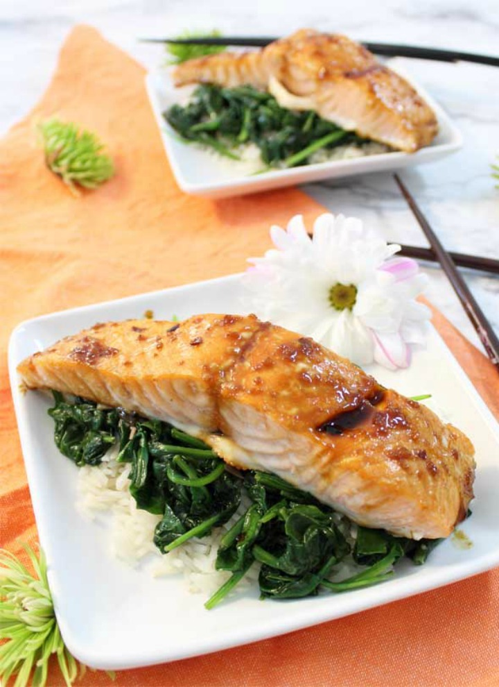 Baked Salmon with greens and white rice for two both served on white plates