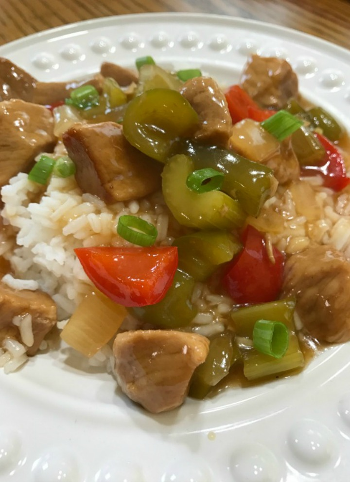 Sweet and Sour Pork served over white rice on a white plate