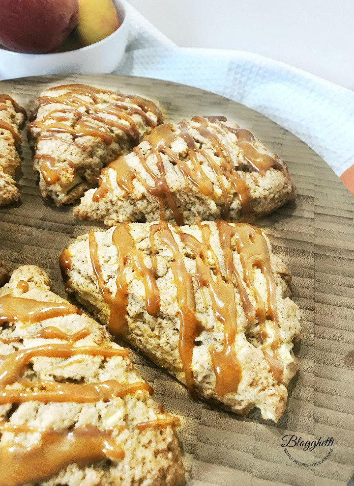 Caramel Apple Scones on a wooden platter with bowl of apples in the background