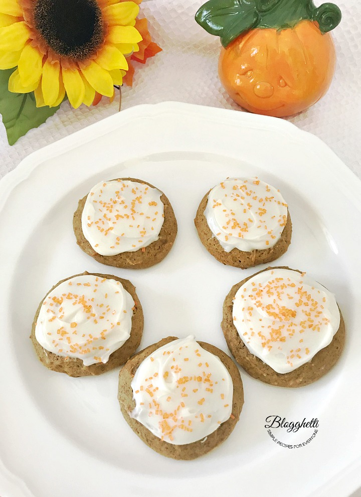 Pumpkin Cookies with Cream Cheese Frosting on a white plate with pumpkin and sunflower in background