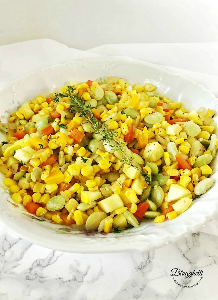 White bowl filled with southern succotash on a marble countertop
