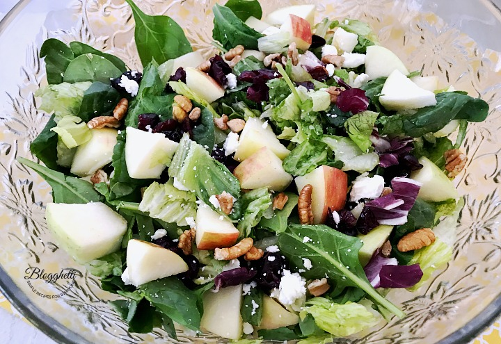 apple cranberry pecan salad with spinach in a crystal bowl