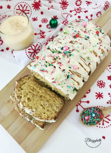 Holiday Eggnog Bread with glass of eggnog and sprinkles