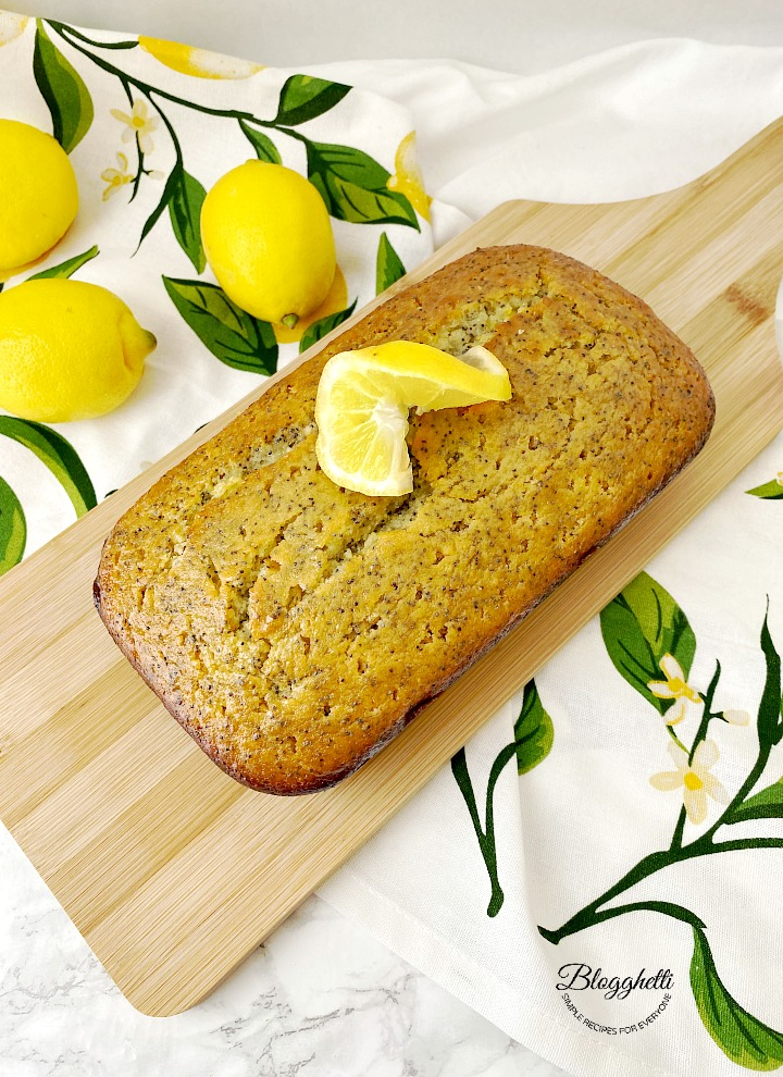 lemon poppy seed bread on wooden board with lemon slice