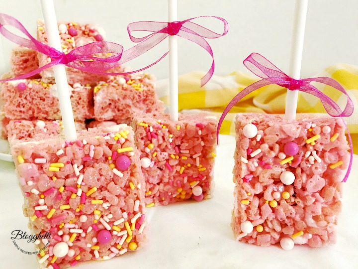 pink lemonade rice krispie treats on lollipop sticks with ribbons