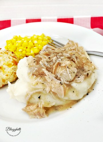 chicken and gravy with mashed potatoes, corn and cheese biscuit on white plate