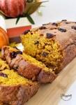 sliced pumpkin cranberry bread on wooden board