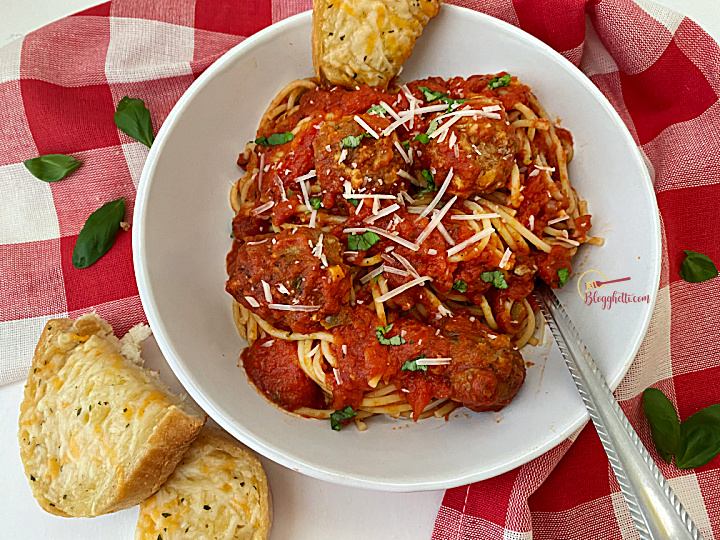 best spaghetti and meatballs in white bowl with garlic bread