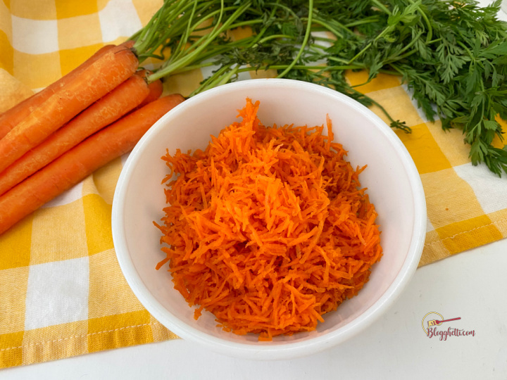 shredded carrots in white bowl with fresh carrots in background
