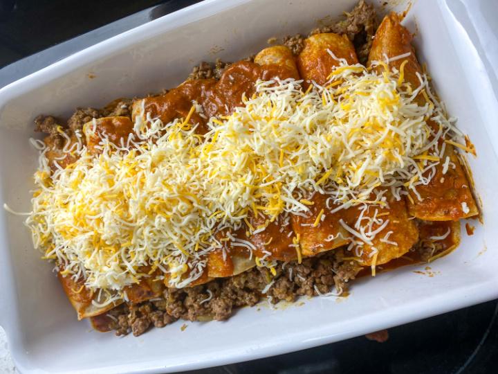 adding cheese on top of the enchiladas