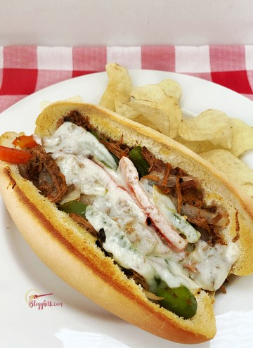 easy philly cheesesteak sandwich with chips on white plate