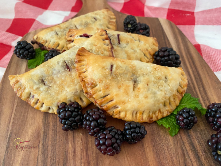 close up of blackberry hand pies on wooden platter