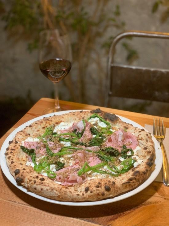 pizza con mortadela trufada, stracciatella de burrata, hojas de espinacas y trufa negra. Copa de vino. Silla metálica.