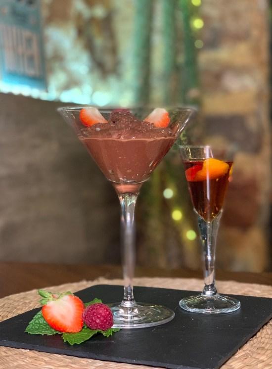 Copa de chocolate, con media fresa y una frambuesa, copa de moscatel de Setúbal