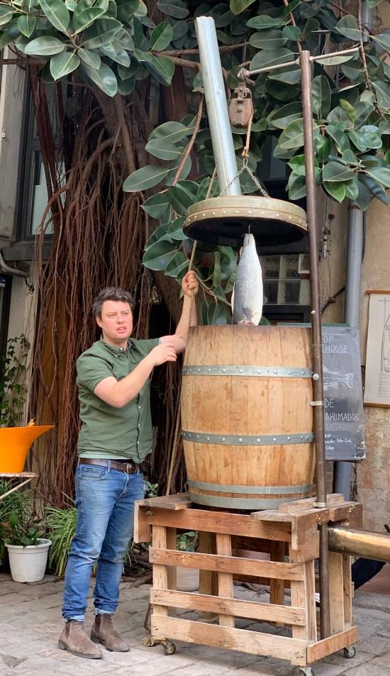 hombre moviendo un barril con una lubina dentro