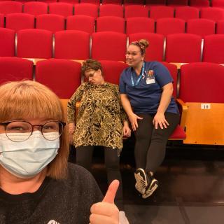 Kolme ihmistä teatterilla.