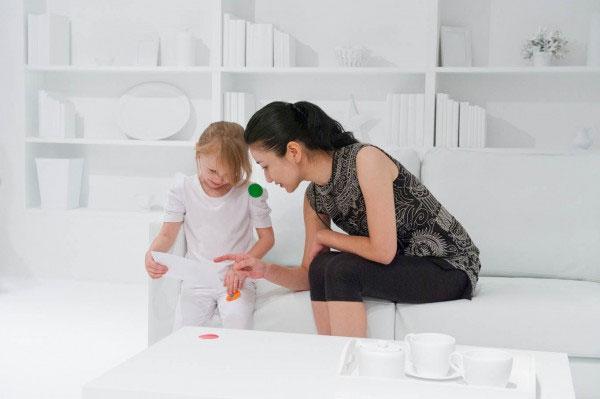 Um quarto todo branco e milhares de crianças com adesivos de bolinhas coloridas
