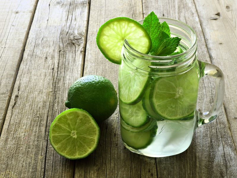 39206740 - detox water with lime and cucumbers in a mason jar against a rustic wood background