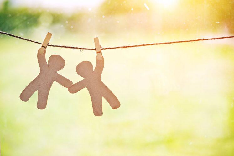 paper dolls holding hands on clothesline support
