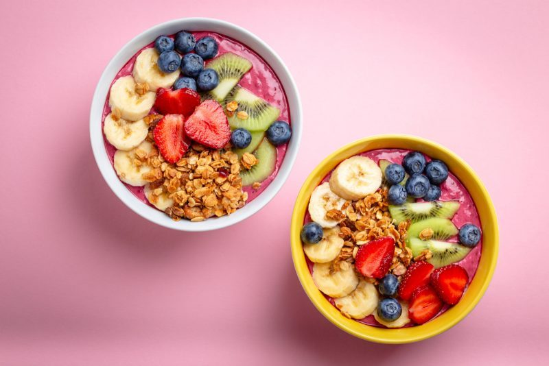 acai bowls with fruit and granola on a pink background