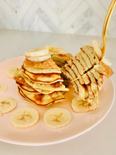 blogilates protein pancakes with sliced banana on pink plate