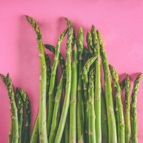asparagus stalks on pink background