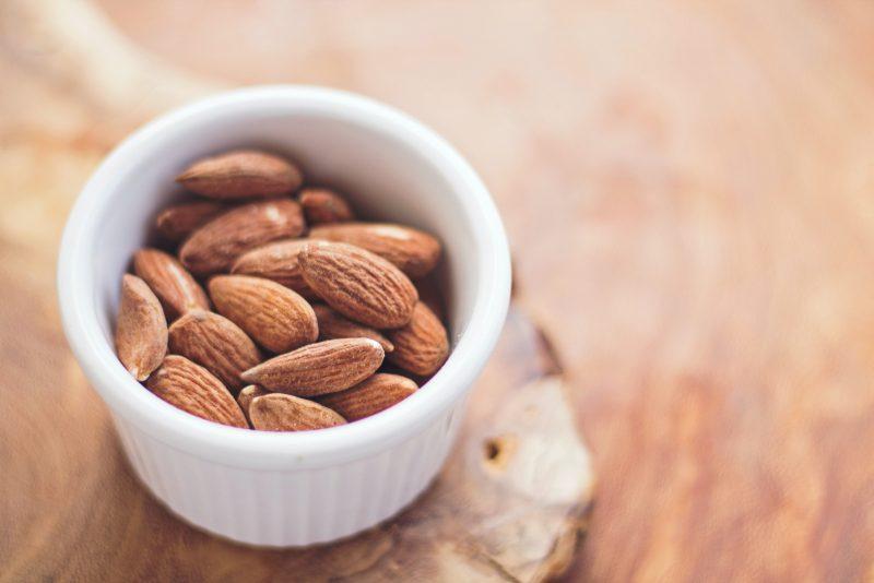 small serving almonds in white ramekin on cutting board